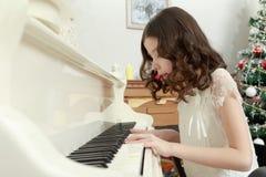 Härlig flicka i ett vitt klänningsammanträde på pianot Arkivbild