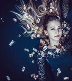 Härlig flicka i guld Blondin i guld- konfettier royaltyfri foto