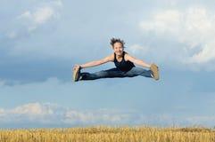 Härlig flicka i gymnastiskt hopp mot den blåa skyen royaltyfri bild