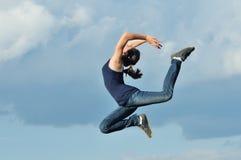 Härlig flicka i gymnastiskt hopp mot den blåa skyen royaltyfria foton