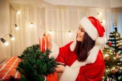 Härlig flicka i hatten av Santa Claus belysningstearinljus på royaltyfri fotografi