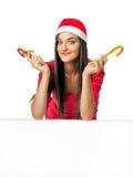 Härlig flicka i a i jultomten en hjälpredahatt som rymmer en godisrotting Royaltyfri Bild