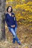 Härlig flicka i jeans med en bok under hans lutande agains för arm Fotografering för Bildbyråer