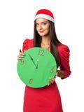 Härlig flicka i jultomten en hjälpredahatt som rymmer en grön klocka Arkivfoton