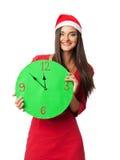 Härlig flicka i jultomten en hjälpredahatt som rymmer en grön klocka Royaltyfria Foton
