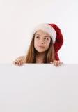 Härlig flicka i jultomtenhatten som rymmer det vita brädet och drömmer aboen Arkivbild