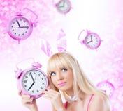 Härlig flicka i kaninöron som rymmer klockan Royaltyfri Bild