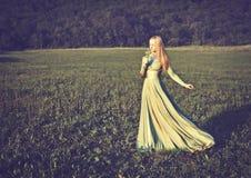 Härlig flicka i klänning för lång gräsplan med buketten av blommor i sommaronnature Royaltyfri Foto