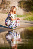 Härlig flicka i klänning på floden Fotografering för Bildbyråer