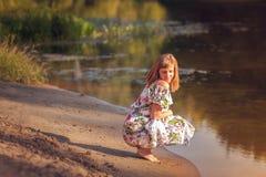 Härlig flicka i klänning på floden Arkivfoto