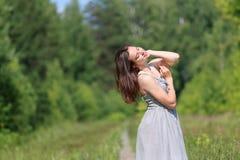 Härlig flicka i klänninganseende på den omgivna vandringsledet Royaltyfria Foton