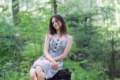 Härlig flicka i klänningsammanträde på stubbe i skog Fotografering för Bildbyråer