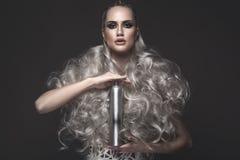 Härlig flicka i konstklänning- och avantgardefrisyrer med kosmetiska produkter i hennes händer Härlig le flicka Arkivfoto