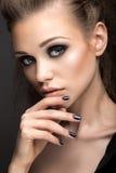 Härlig flicka i läderomslag med ljusa makeup- och manikyrkatts öga Härlig le flicka Spika designen Arkivfoton