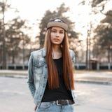 Härlig flicka i modegrov bomullstvillkläderna på en solnedgångbackgrou royaltyfri foto