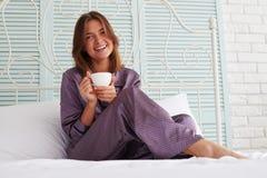 Härlig flicka i natt-dräkt sammanträde på sängkanten med en koppnolla Royaltyfri Foto