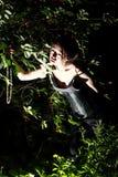 Härlig flicka i natt i busken som in camera ser Royaltyfri Foto