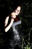 Härlig flicka i natt i busken som ner ser på något Royaltyfria Bilder