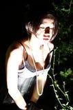 Härlig flicka i natt i busken som ner ser på något, hand Arkivfoto
