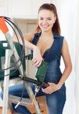 Härlig flicka i overaller med drillborren Royaltyfria Bilder