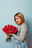Härlig flicka i overallerna med röda rosor i händer på en blå bakgrund Händer för kvinna` s rymmer en bukett av Fotografering för Bildbyråer