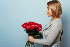 Härlig flicka i overallerna med röda rosor i händer på en blå bakgrund Händer för kvinna` s rymmer en bukett av Arkivbilder