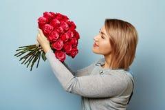 Härlig flicka i overallerna med röda rosor i händer på en blå bakgrund Händer för kvinna` s rymmer en bukett av Royaltyfri Bild