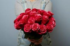 Härlig flicka i overallerna med röda rosor i händer på en blå bakgrund Händer för kvinna` s rymmer en bukett av Royaltyfria Foton