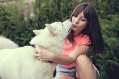 Härlig flicka i parkera som spelar med hennes skrovliga hund Royaltyfria Bilder