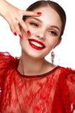 Härlig flicka i röd klänning med klassiskt smink och röd manikyr Härlig le flicka arkivbild