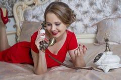 Härlig flicka i röd klänning som talar på telefonen royaltyfria bilder