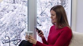 Härlig flicka i rött klänningsammanträde på fönsterbrädan som dricker te och ser fönstret utvändig vinter lager videofilmer
