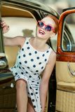 Härlig flicka i retro stil och en tappningbil royaltyfria foton