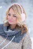 Härlig flicka i rosa hörlurar på halsduken med snö Arkivfoto