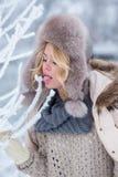 Härlig flicka i rosa hörlurar på halsduken med snö Arkivbild