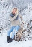 Härlig flicka i rosa hörlurar på halsduken med snö Arkivfoton