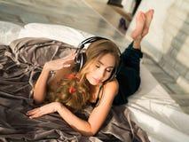 Härlig flicka i sleepwear som ler att lyssna till musik i hörlurar som ligger på säng Från över Arkivfoton
