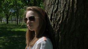 Härlig flicka i solglasögon i parkera Flickatonåringnärbild på naturen Flicka i fräknar och exponeringsglas på en solig dag lager videofilmer