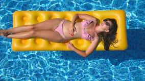 Härlig flicka i solglasögon och bikinin som ligger på den gula uppblåsbara madrassen i simbassäng brunbränt kvinnabarn stock video