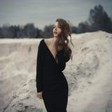 Härlig flicka in i svart tappningklänning med lockigt hår som poserar på sanden Kvinna i retro dres Bekymrad sinnlig sinnesrörels fotografering för bildbyråer