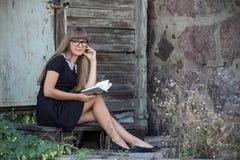 Härlig flicka i svarta exponeringsglas som läser en bok Arkivbild