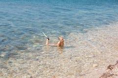 Härlig flicka i tillbehör för att dyka i klart havsvatten Royaltyfri Foto