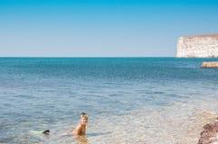 Härlig flicka i tillbehör för att dyka i klart havsvatten Royaltyfria Bilder