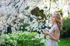 Härlig flicka i trädgård för körsbärsröd blomning arkivfoton