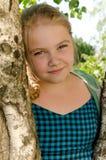 Härlig flicka i trädgården nära trädet som är tonårigt Fotografering för Bildbyråer