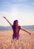 Härlig flicka i vetefält på solnedgången Fotografering för Bildbyråer
