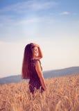 Härlig flicka i vetefält på solnedgången Arkivbild