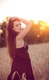 Härlig flicka i vetefält på solnedgången Arkivbilder