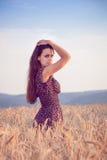 Härlig flicka i vetefält på solnedgången Royaltyfri Foto