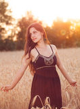 Härlig flicka i vetefält på solnedgången Royaltyfri Bild